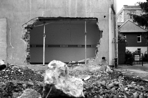 black and white photo of a building with a hole in the wall