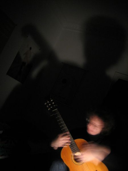 My flatmate playing the guitar with a huge shadow behind him
