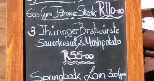 Menu listing 'Thüringer Bratwürste' next to T-Bone Steak and Springbok Loin