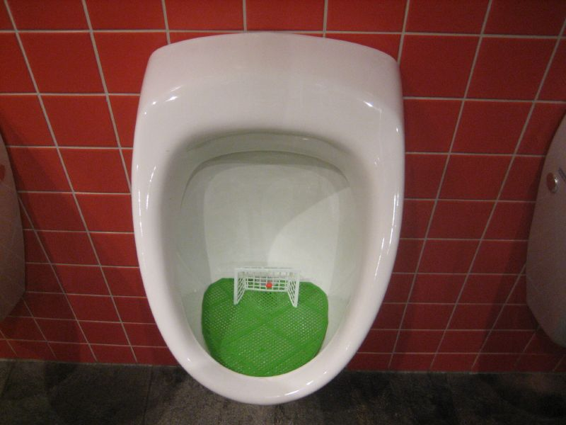 Urinal with a football goal inside