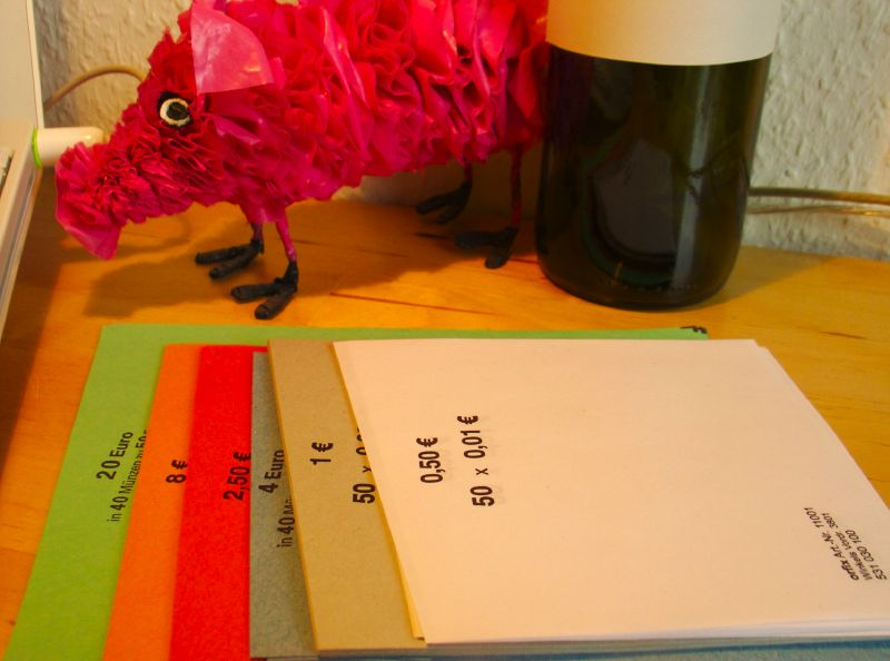 Coloured sheets of paper to roll the money into. A pink pig looking at everything sceptically.