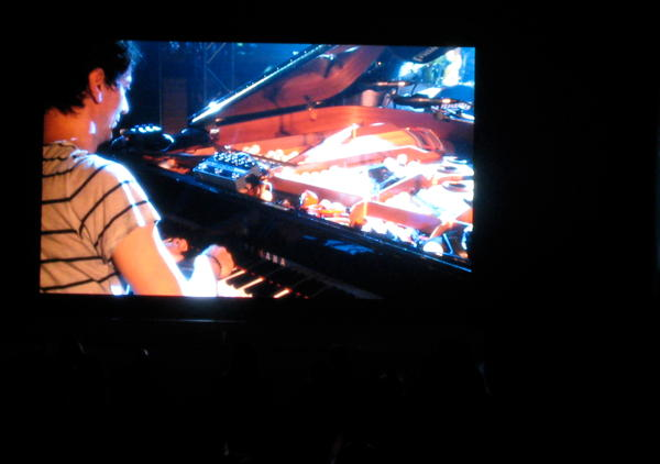 Hauschka on a grand piano with table tennis balls, projected on the screen outside the Spiegelzelt at Haldern Pop 2011