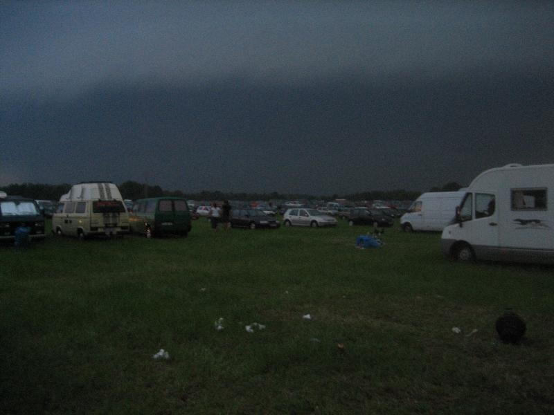 meadow with cars on it under a dark grey sky