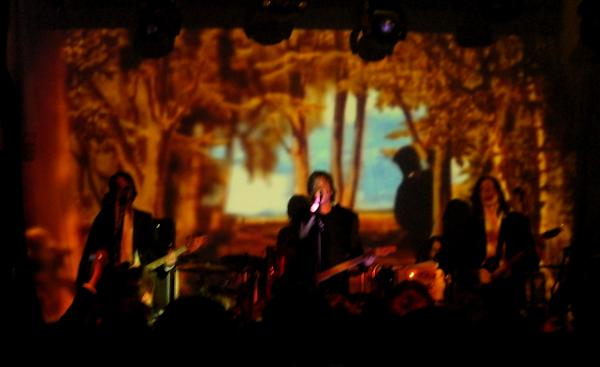 Mew on stage with a projected scene behind them.