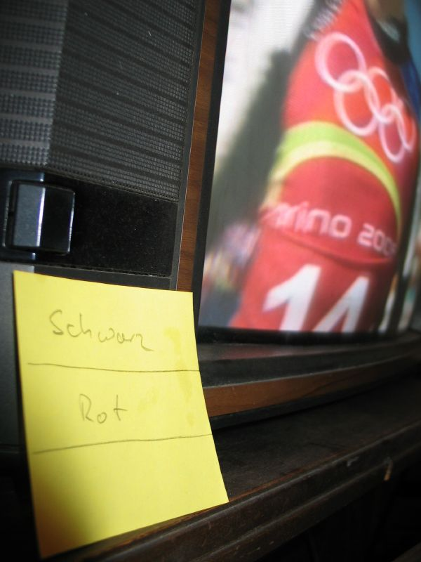 Photo of the telly with a yellow post-it note stuck to it which has 'schwarz' (black) written on its top third and Rot (red) written on the middle third to give the mockup of a German flag