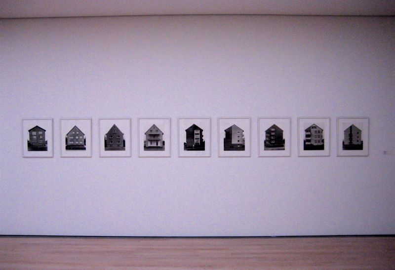 Nine similar black and white photos of nine similar houses - hung in a row