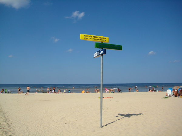 Beach in Dubulti with signs pointing to the 'active' and 'passive' recreation areas.