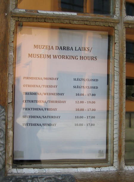 Opening Times on a paper sheet behind a window.