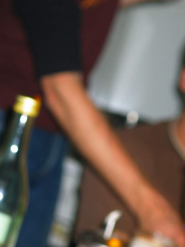 blurry arm, behind a bottle