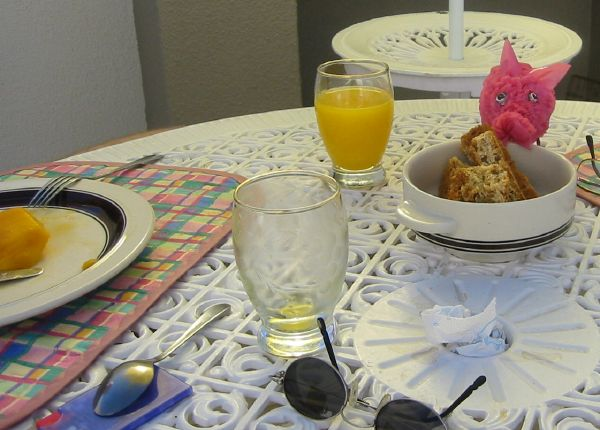 Breakfast table on the balcony with mango, orange juice and a pink pig eating rusks