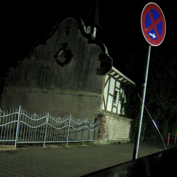 a strange house and a street sign in the dark