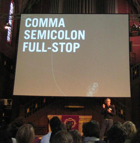 Brendan Dawes speaking at see conference 2011 with a slide saying »Comma, Semicolon, Full Stop« in the background