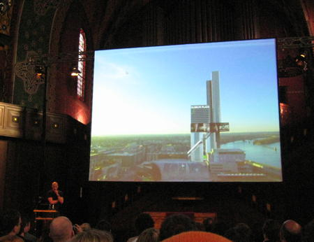 Joshua Prince-Rasmus speaking at see conference 2011 with a slide showing a model of their building for University of Louisville embedded into the city in the background