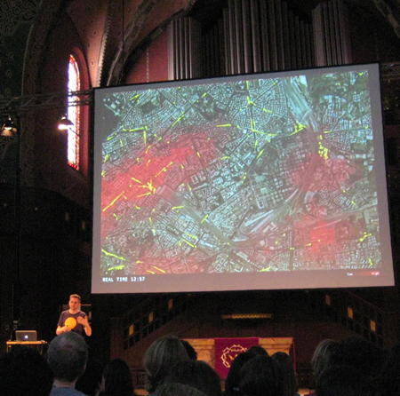 Carlo Ratti sepaking at see conference 2011 with a slide showing a map of Rome with information about mobile phone locations and bus locations in the background