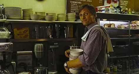 Shot from history of violence - Tom carrying some plates in his diner.