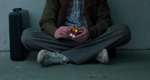 A shot from the film with a geeky detective easily identified by the Rubik's cube he holds