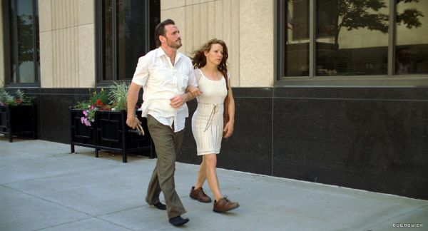 shot from the film, Henry Chinaski and his girlfriend walking down the sidewalk, she's wearing his shoes