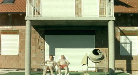 Couple subathing on their terrace next to a concrete mixer