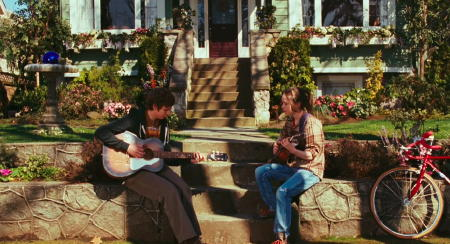 Shot from the film with Juno and Paulie playing guitar in the garden
