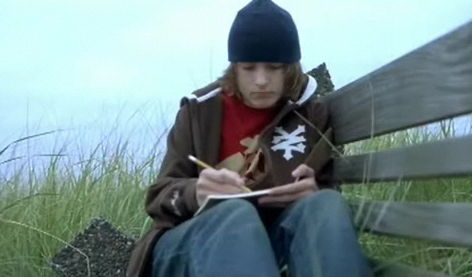 Alex writing a letter on a bench